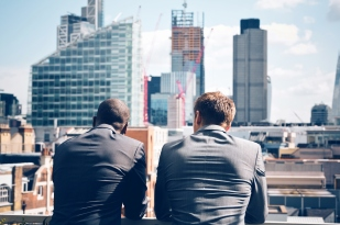 Two businessmen looking at city scape